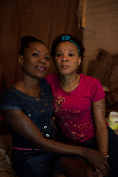 Lufuno Nevhulaudzi poses for a picture with her friend, Yanga Mpengu, a two year resident, in her basement room at the Moth building in Joubert Park on Wednesday, Aug. 5, 2015. The residents here were evicted from their previous building in New Town to make way for a new mall under construction.