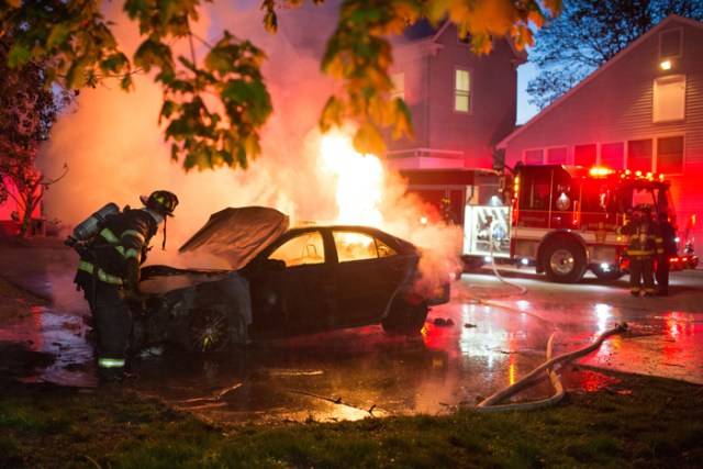 Firefighters extinguish a car fire in the parking lot of Health Service on Monday, May 9, 2016. The fire accompanied bomb threats which caused cancellations of final exams campus-wide.