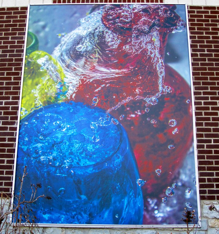 February 1st. Poster of colored liquids on building.