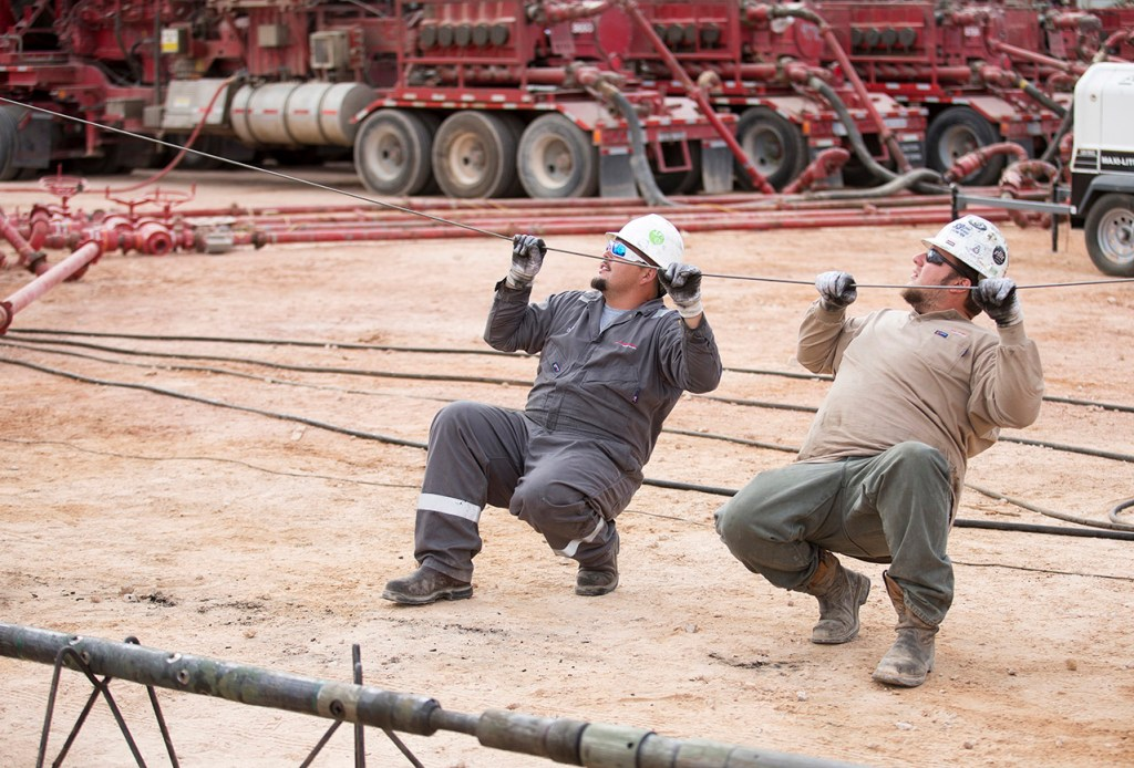 Arklatex Energy Services field hands align the wireline while on location, Monday, Aug. 22, 2016, in Andrews, Texas.