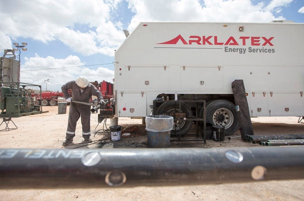 An Arklatex Energy Services field hand puts together the perforating gun while on location, Monday, Aug. 22, 2016, in Andrews, Texas.