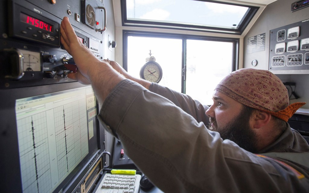 An Arklatex Energy Services engineer fires a set of guns from a control panel while on location, Monday, Aug. 22, 2016, in Andrews, Texas.