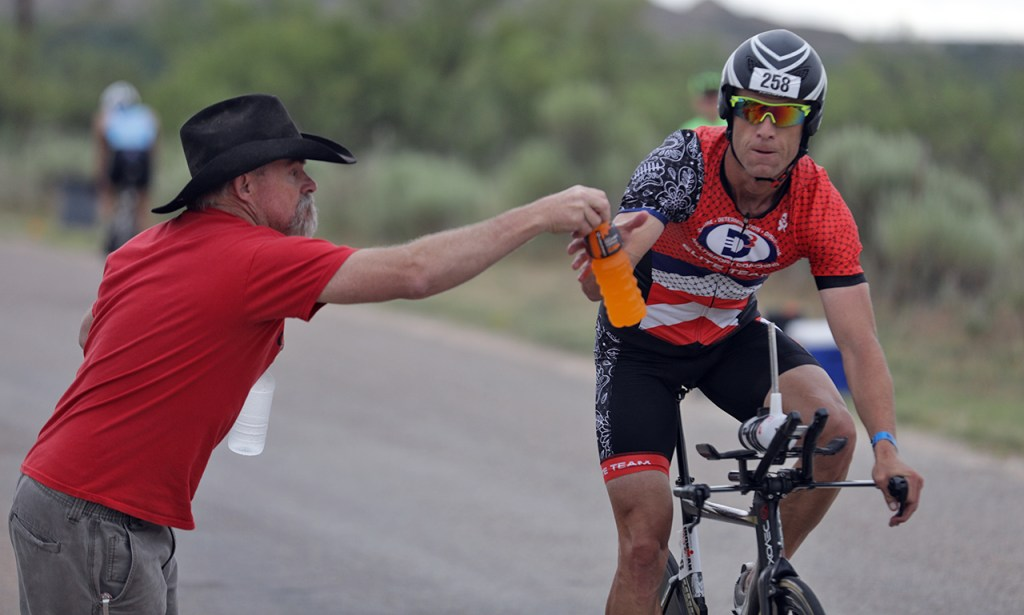 James Hallberg, from Longmont, Colo., grabs a bottle from a volunteer during the Ironman 70.3 Buffalo Springs Lake, Sunday, June 25, 2017, at Buffalo Springs Lake in Buffalo Springs, Texas. (Brad Tollefson/A-J Media)