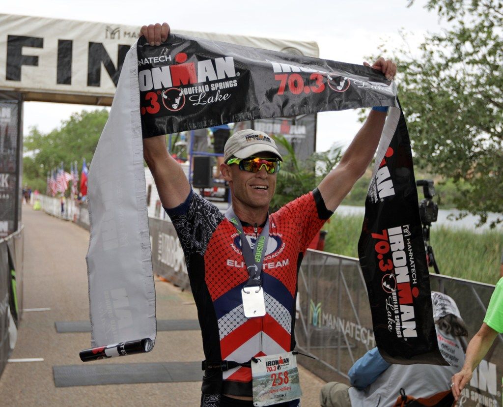 James Hallberg, from Longmont, Colo., holds the banner as the first contestant to cross the finish line during the Ironman 70.3 Buffalo Springs Lake, Sunday, June 25, 2017, at Buffalo Springs Lake in Buffalo Springs, Texas. (Brad Tollefson/A-J Media)