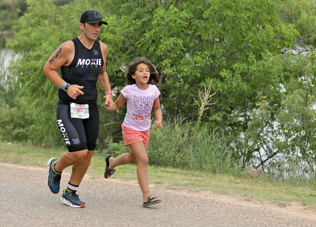 Kobi Otero runs beside her father Pete Otero, from Pflugerville, in the final stretch of the race during the Ironman 70.3 Buffalo Springs Lake, Sunday, June 25, 2017, at Buffalo Springs Lake in Buffalo Springs, Texas. (Brad Tollefson/A-J Media)