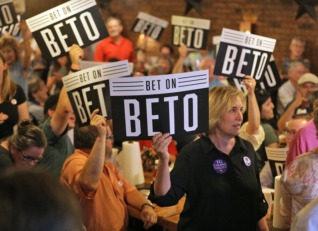 Supporters hold up signs for U.S. Rep. Beto O'Rourke as he walks into the restaurant during a campaign stop Monday, July 3, 2017, at J&M Bar-B-Q in Lubbock, Texas. O'Rourke is a democrat running for the senate seat held by Ted Cruz. (Brad Tollefson/The Texas Observer)