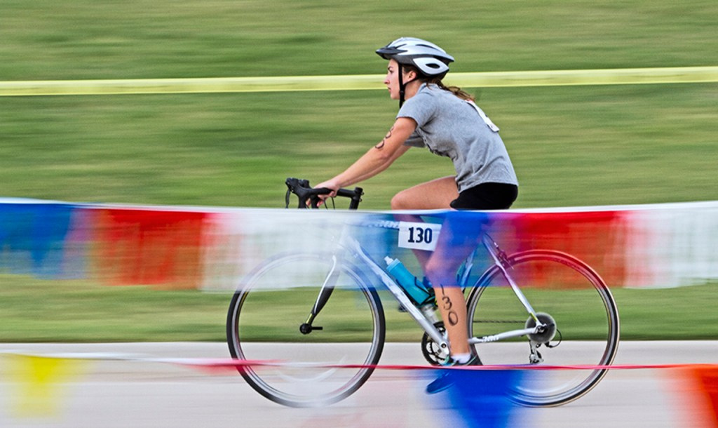 Danielle Hill coasts her bike in the transition zone while finishing the cycling leg of the Rec Sports Triathlon on Sunday, Sept. 9, 2012, outside the Robert H. Ewalt Student Recreation Center. Transition zones were provided to allow competitors a place to prepare for different legs of the triathlon.