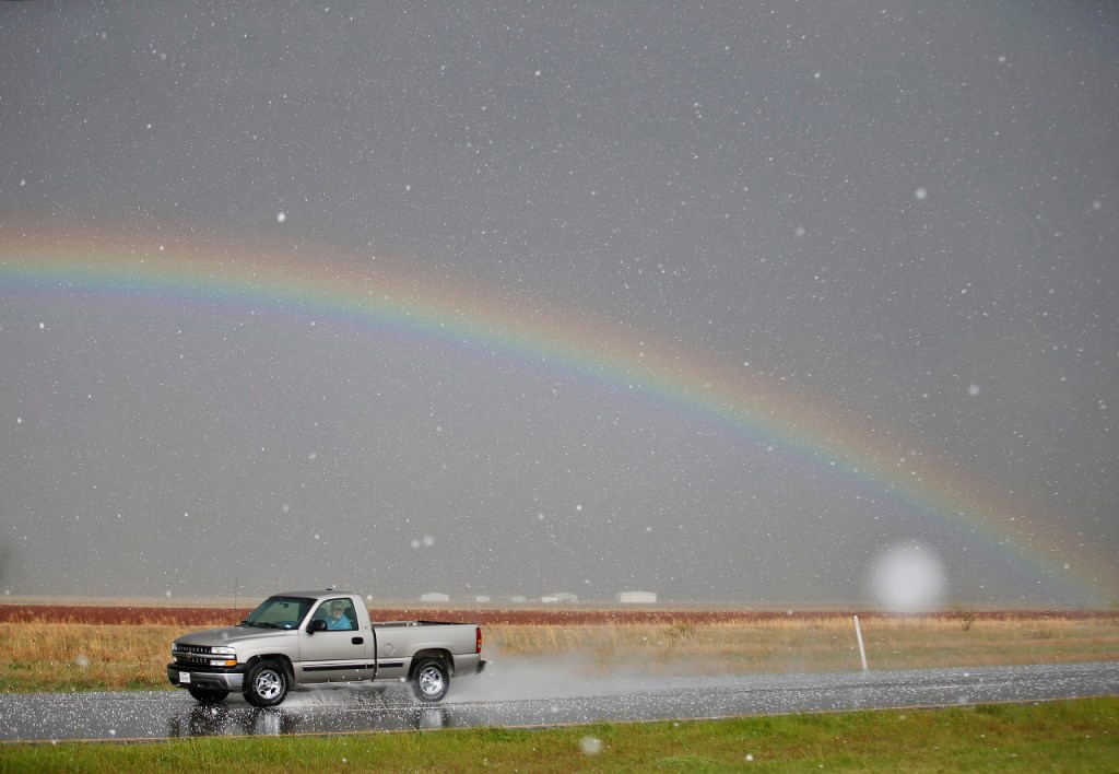 A rainbow appears in the sky while hail falls on the road during a storm near Floydada, Texas, on Thursday, April 28, 2016.