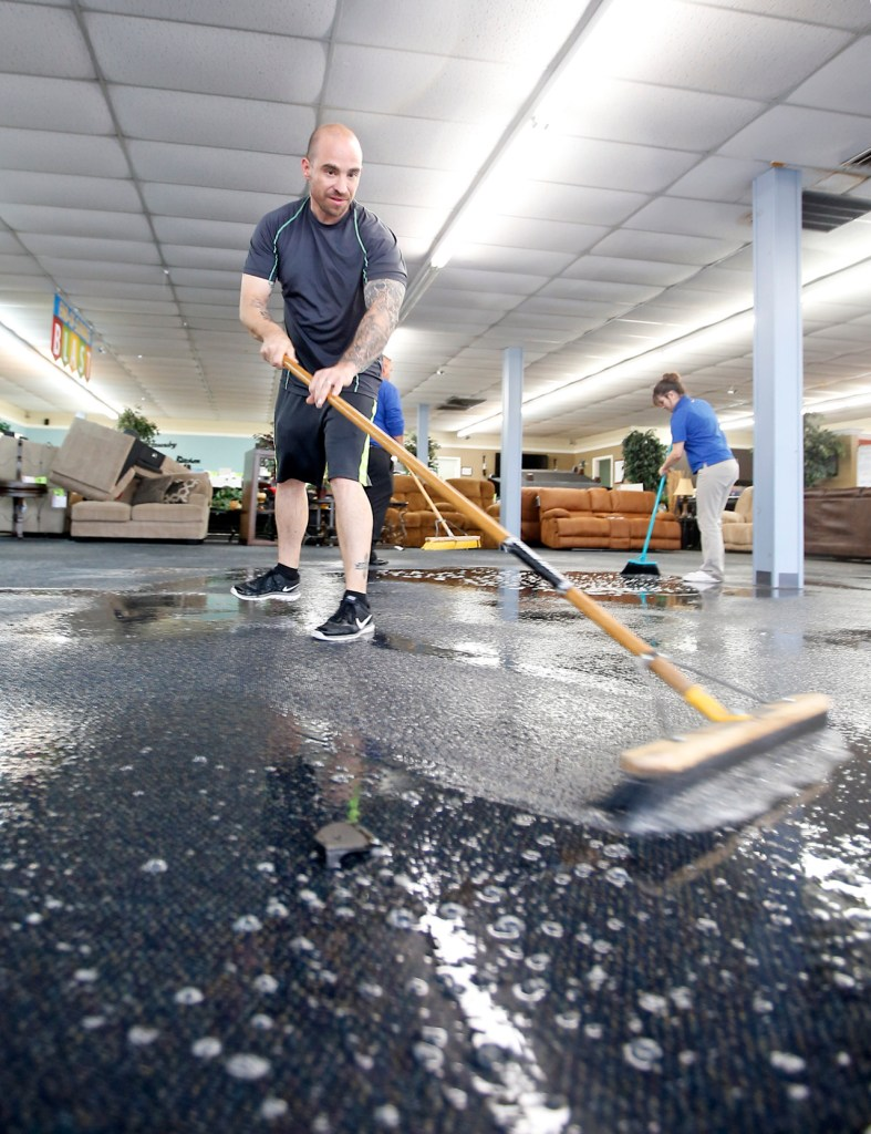 Brian Tilden, from Lubbock, sweeps rain water across the floor Wednesday, Aug. 31, 2016, at Rent-A-Center near 34th Street and University Avenue in Lubbock, Texas.