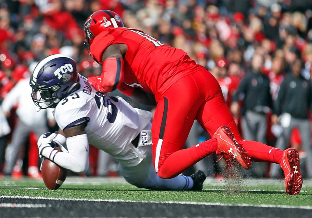 TCU's Sewo Olonilua dives on the fumbled ball away from from Texas Tech's Kolin Hill