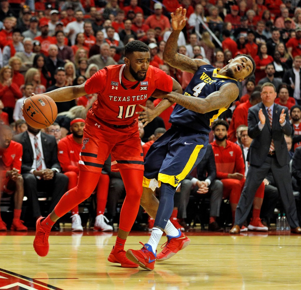 Texas Tech's Niem Stevenson (10) pushes away West Virginia's Daxter Miles (4) during the first half of an NCAA college basketball game Saturday, Jan. 13, 2018, in Lubbock, Texas. (AP Photo/Brad Tollefson)