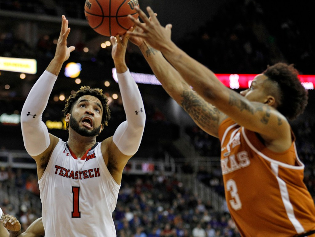 Texas Tech's Brandone Francis (1) and Texas' Jacob Young (3) reach for a loose ball during a Big 12 basketball tournament game Thursday, March 8, 2018, at the Sprint Center in Kansas City, Mo. [Brad Tollefson/A-J Media]
