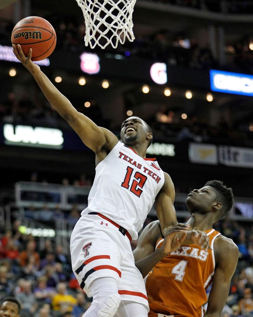 Texas Tech's Keenan Evans (12) lays up the ball over Texas' Mo Bamba (4) during a Big 12 basketball tournament game Thursday, March 8, 2018, at the Sprint Center in Kansas City, Mo. [Brad Tollefson/A-J Media]