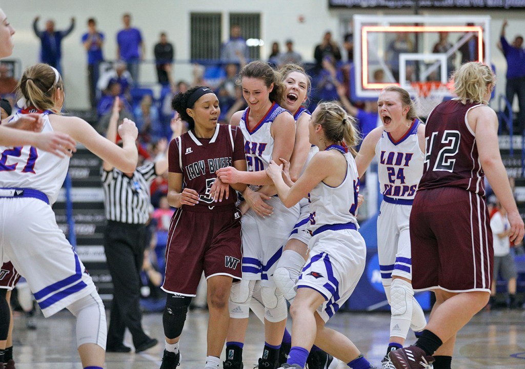 Lubbock Christian players celebrate with Olivia Robertson (20) after she scored a half-court shot at halftime during the South Central regional championship against West Texas A&M, Monday, March 12, 2018, at Rip Griffin Center in Lubbock, Texas. [Brad Tollefson/A-J Media]