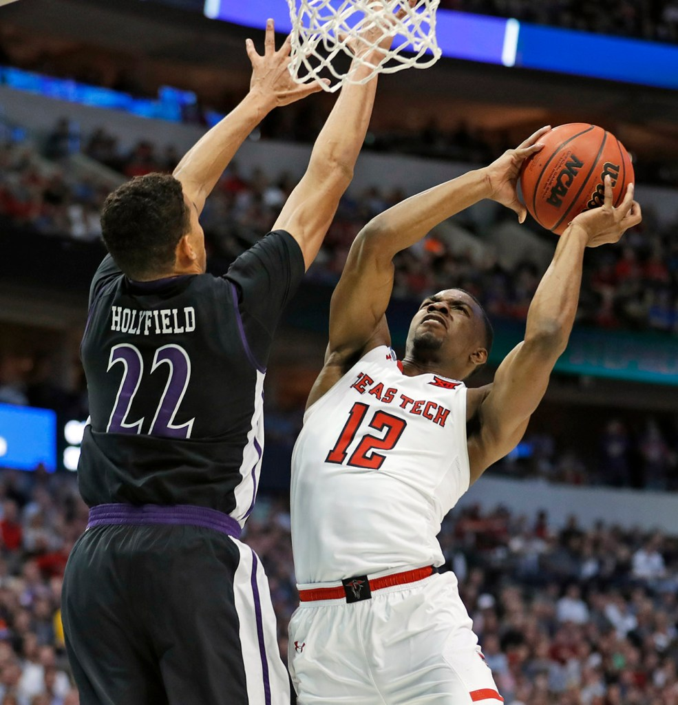 Texas Tech's Keenan Evans (12) shoots the ball around Stephen F. Austin's TJ Holyfield (22) during an NCAA college basketball tournament first-round game Thursday, March 15, 2018, at American Airlines Center in Dallas, Texas. [Brad Tollefson/A-J Media]