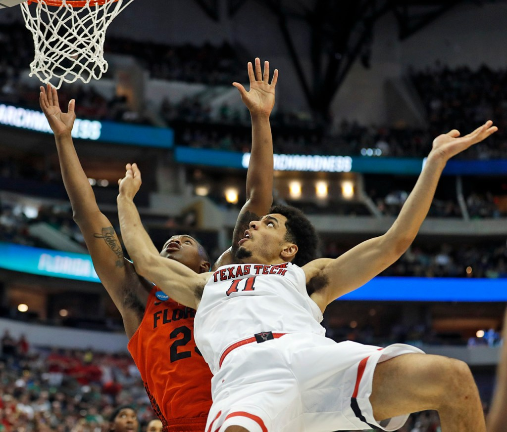 Texas Tech's Zach Smith (11) falls down on Florida's Keith Stone (25) during an NCAA college basketball tournament second-round game Saturday, March 17, 2018 at American Airlines Center in Dallas, Texas. [Brad Tollefson/A-J Media]