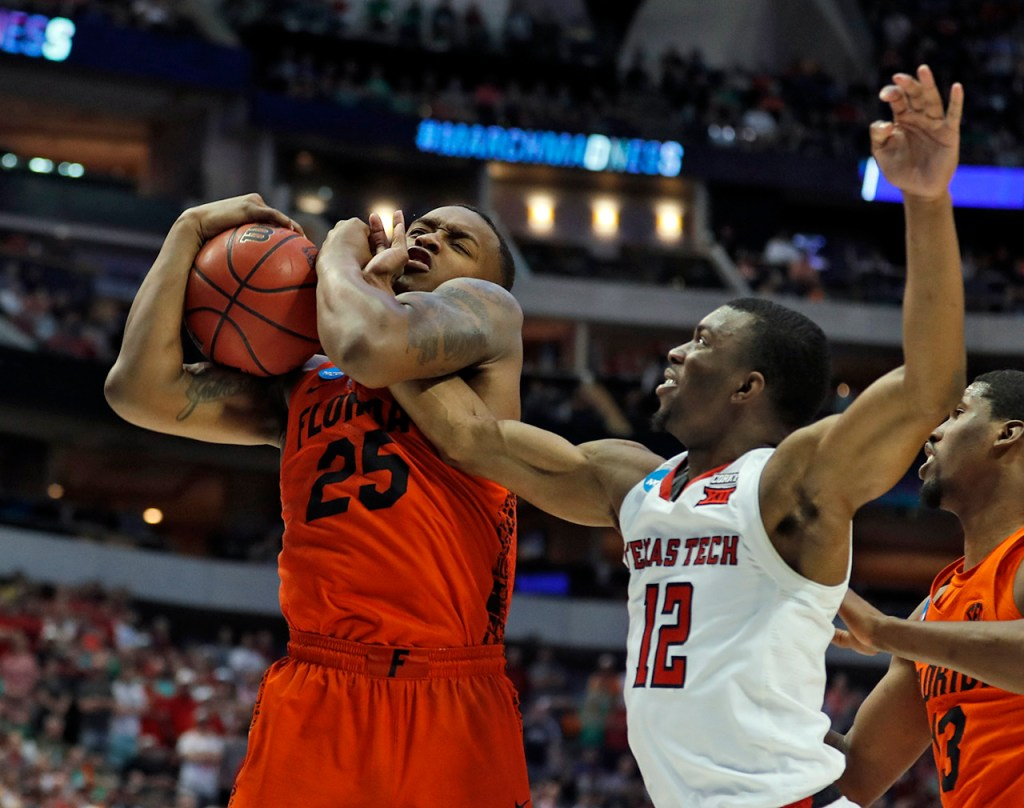 Florida's Keith Stone (25) rebounds the ball away from Texas Tech's Keenan Evans (12) during an NCAA college basketball tournament second-round game Saturday, March 17, 2018 at American Airlines Center in Dallas, Texas. [Brad Tollefson/A-J Media]