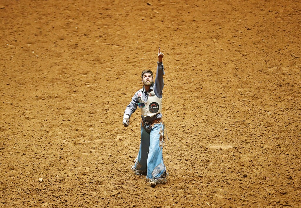Luke Creasy, from Hobbs, N.M., points to the sky after the bareback competition during the ABC Pro Rodeo, Friday, March 30, 2018, at Municipal Coliseum in Lubbock, Texas. [Brad Tollefson/A-J Media]