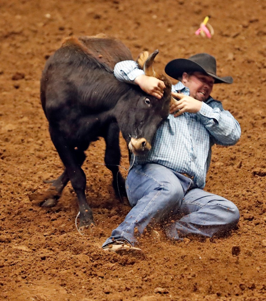 Mitchell Gardner (107) wrestles the steer during the ABC Pro Rodeo, Friday, March 30, 2018, at Municipal Coliseum in Lubbock, Texas. [Brad Tollefson/A-J Media]
