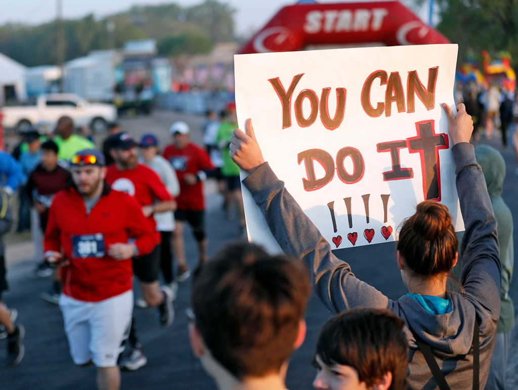 Tia Pratt, from Lubbock, holds up a sign supporting the competitors in the full marathon during the Mayor's Marathon, Sunday, April 22, 2018, at Berl Huffman Athletic Complex in Lubbock, Texas. [Brad Tollefson/A-J Media]