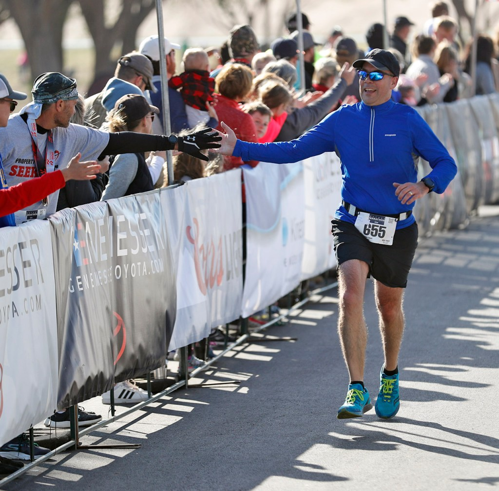 Kevin Wass (655) high-fives the crowd while finishing the half marathon race during the Mayor's Marathon, Sunday, April 22, 2018, in Lubbock, Texas. [Brad Tollefson/A-J Media]