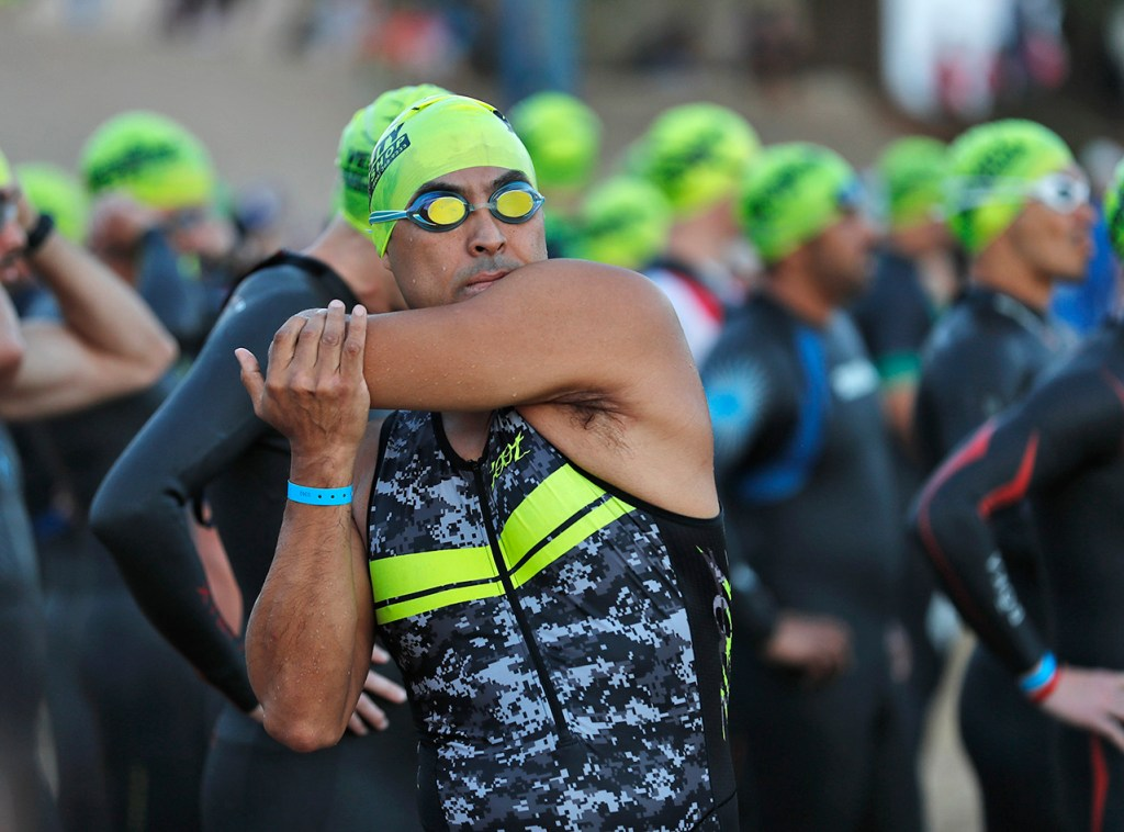 Edward Martinez (362) stretches before the race begins during the Ironman 70.3 Buffalo Springs Lake, Sunday, June 24, 2018, in Buffalo Springs, Texas. [Brad Tollefson/A-J Media]