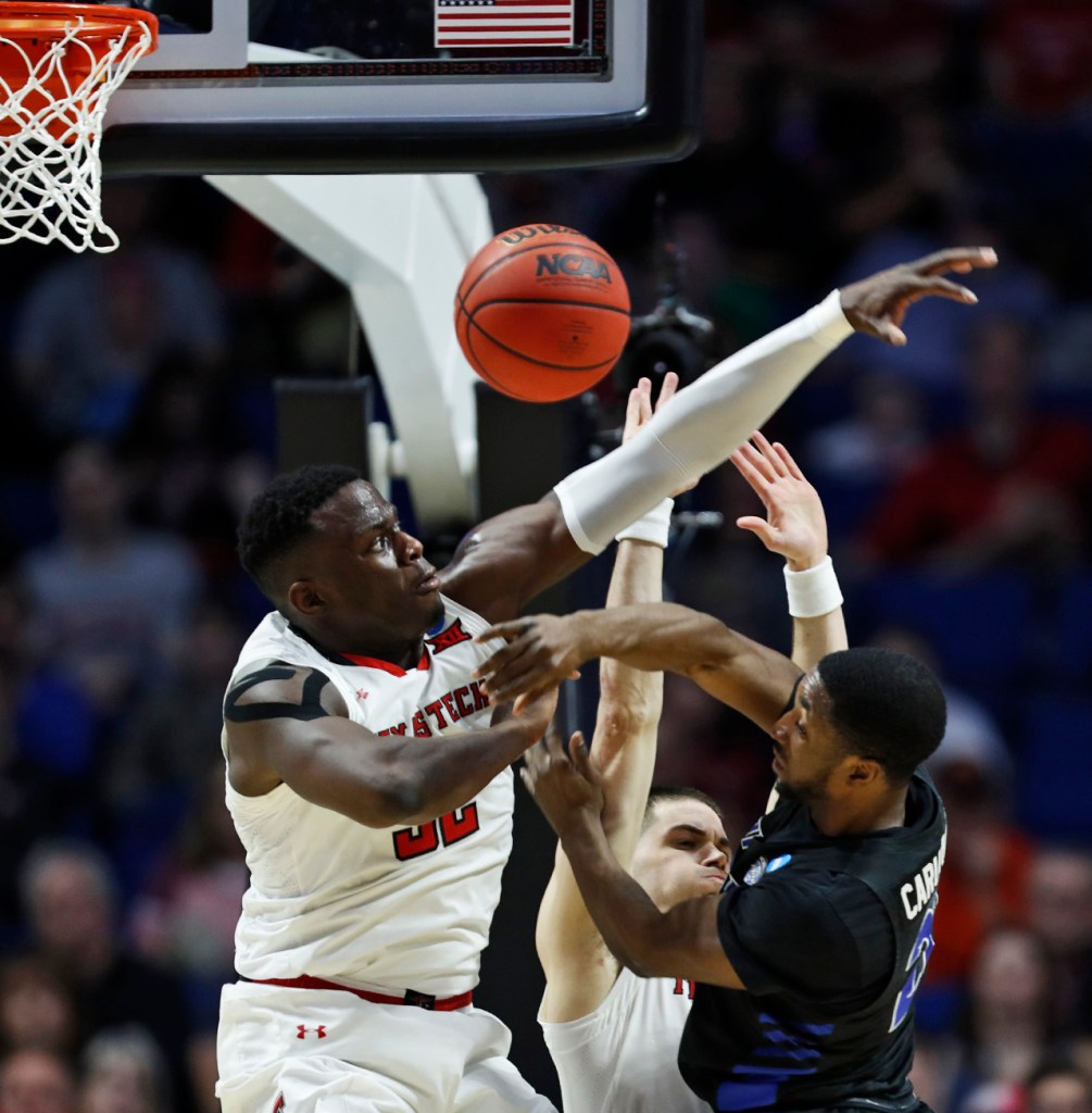 Texas Tech's Norense Odiase (32) blocks a shot by Buffalo's Dontay Caruthers (22) during the NCAA tournament second round game Sunday, March 24, 2019, at BOK Center in Tulsa, Okla. [Brad Tollefson/A-J Media]