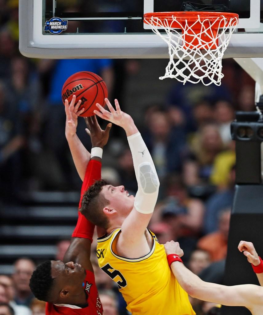 Texas Tech's Norense Odiase (32) fouls Michigan's Jon Teske (15) as he shoots the ball during the NCAA tournament Sweet 16 game Thursday, March 28, 2019, at Honda Center in Anaheim, Calif. [Brad Tollefson/A-J Media]