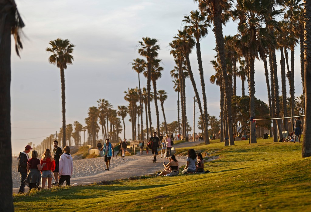 Tourists walk along the beach and palm trees Sunday, March 31, 2019, in Huntington Beach, Calif. (Brad Tollefson)
