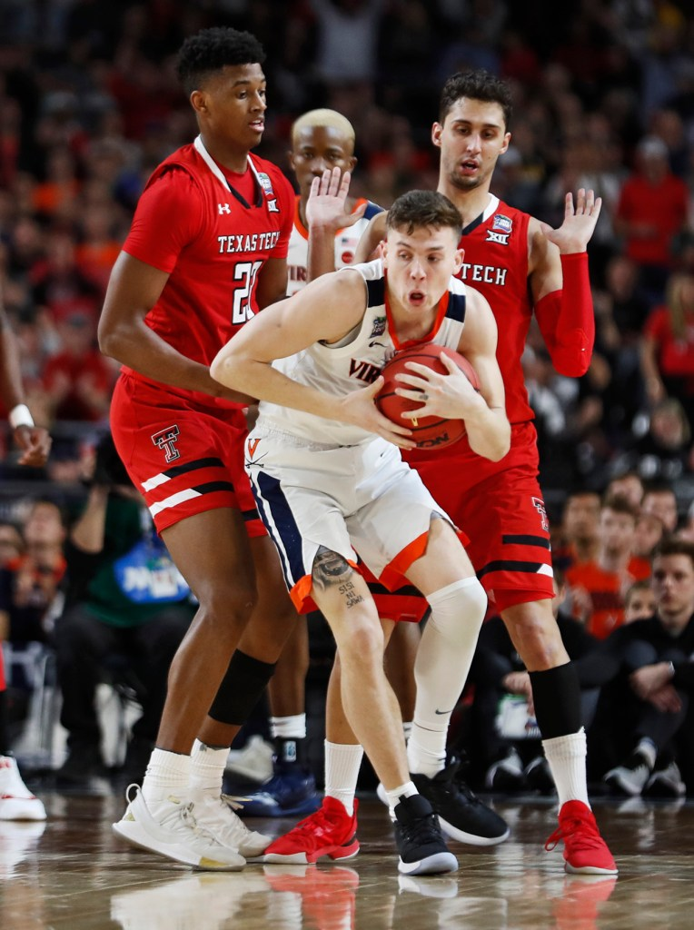Virginia's Kyle Guy (5) takes the ball from Texas Tech's Jarrett Culver (23) and Davide Moretti (25) during the men's basketball national championship against Virginia, Monday, April 8, 2019, at U.S. Bank Stadium in Minneapolis, Minn. [Brad Tollefson/A-J Media]