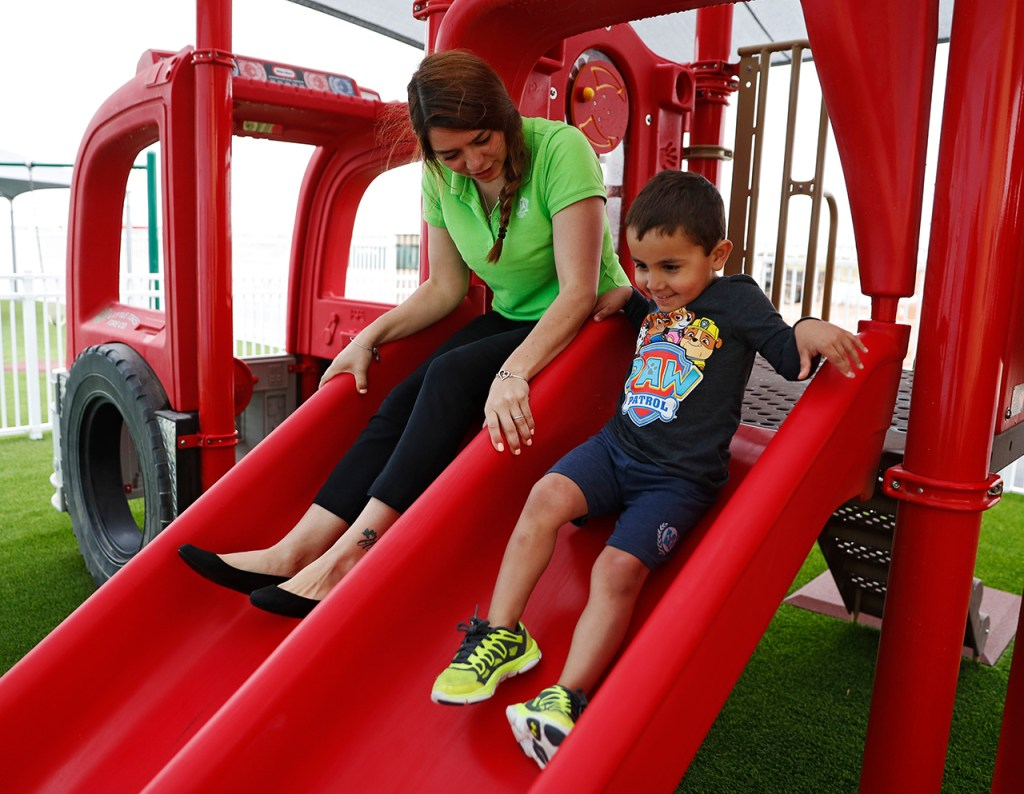 Ashley Doan rides down a slide next to Brycen Shoemake while playing on the slide Primrose School of Midland at Westridge on Tuesday, April 23, 2019 in Midland, Texas. (Brad Tollefson/AP Images for Primrose Schools)