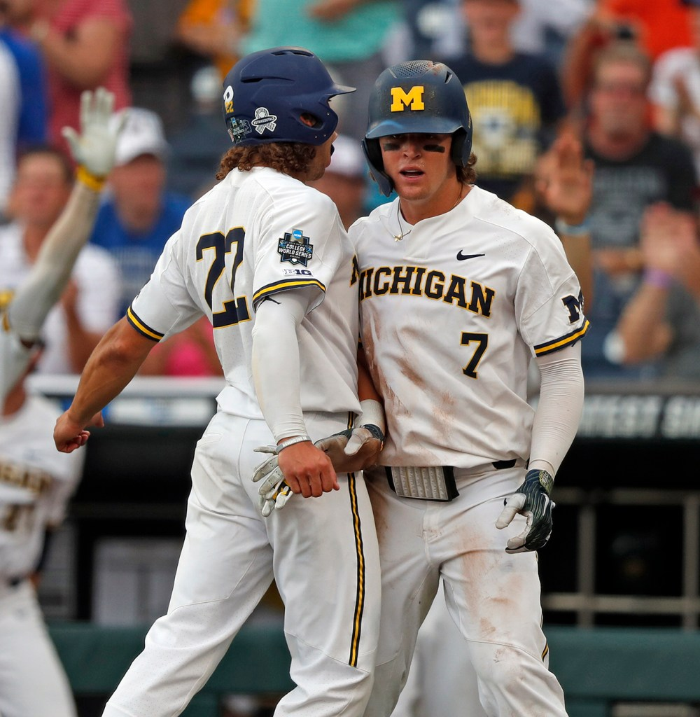Michigan's Jordan Brewer (22) and Jesse Franklin (7) celebrate after scoring runs during the College World Series game against Michigan, Saturday, June 15, 2019, at TD Ameritrade Park in Omaha, Neb. [Brad Tollefson/A-J Media]