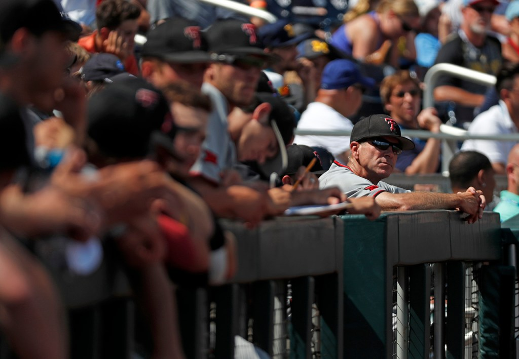 Texas Tech coach Tim Tadlock watches the game from the dugout during the College World Series game against Michigan, Friday, June 21, 2019, at TD Ameritrade Park in Omaha, Neb. [Brad Tollefson/A-J Media]