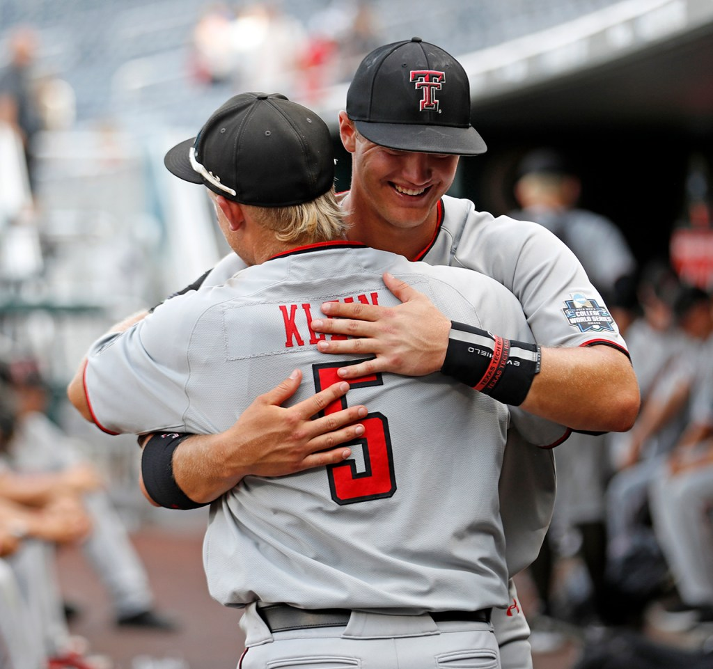 Texas Tech's Brian Klein (5) and Josh Jung (16) hug each other in the dugout after the College World Series game against Michigan, Friday, June 21, 2019, at TD Ameritrade Park in Omaha, Neb. [Brad Tollefson/A-J Media]