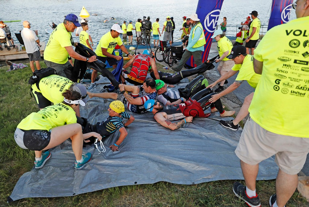 Volunteers help remove the wetsuits from participants during the Ironman 70.3 Lubbock, Sunday, June 30, 2019, at Dunbar Lake in Lubbock, Texas. [Brad Tollefson/A-J Media]
