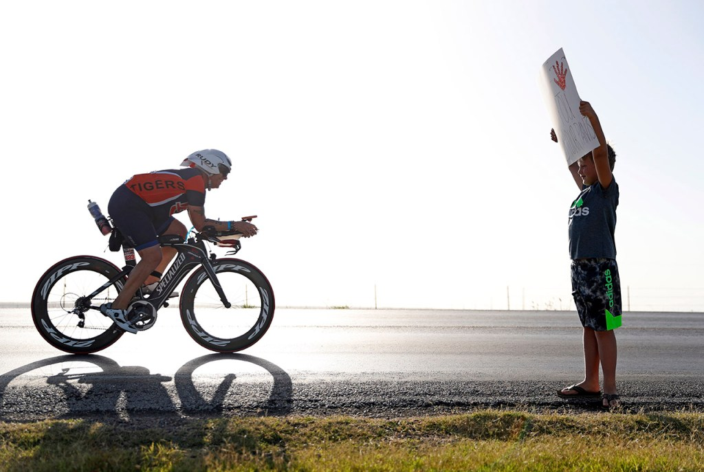 """Simon Manning, from Plainview, holds up a sign that reads """"Wave if you peed your pants"""" as David Pritchett, from Richmond, rides by during the Ironman 70.3 Lubbock, Sunday, June 30, 2019, near Slaton, Texas. [Brad Tollefson/A-J Media]"""