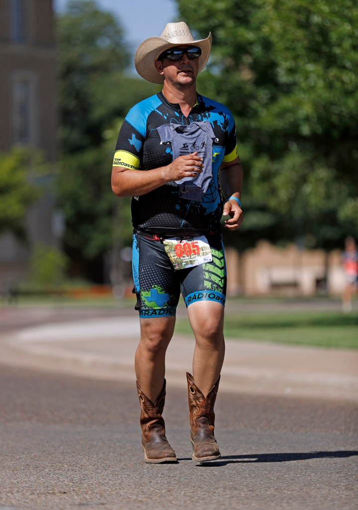 Julian Rangel, from Smithville, runs through campus while wearing cowboy boots during the Ironman 70.3 Lubbock, Sunday, June 30, 2019, at Texas Tech in Lubbock, Texas. [Brad Tollefson/A-J Media]