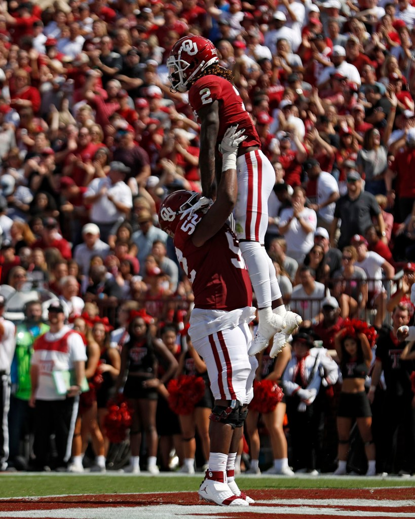 Oklahoma's Tyrese Robinson (52) lifts up CeeDee Lamb (2) after scoring a touchdown during the game against Texas Tech, Saturday, Sept. 28, 2019, at Gaylord Memorial Stadium in Norman, Okla. [Brad Tollefson/A-J Media]