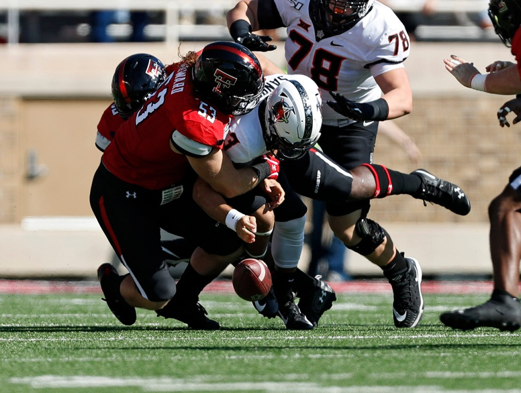 Texas Tech's Eli Howard (53) forces a fumble as he sacks Oklahoma State's Spencer Sanders (3) during the game Saturday, Oct. 5, 2019, in Lubbock, Texas. (AP Photo/Brad Tollefson)