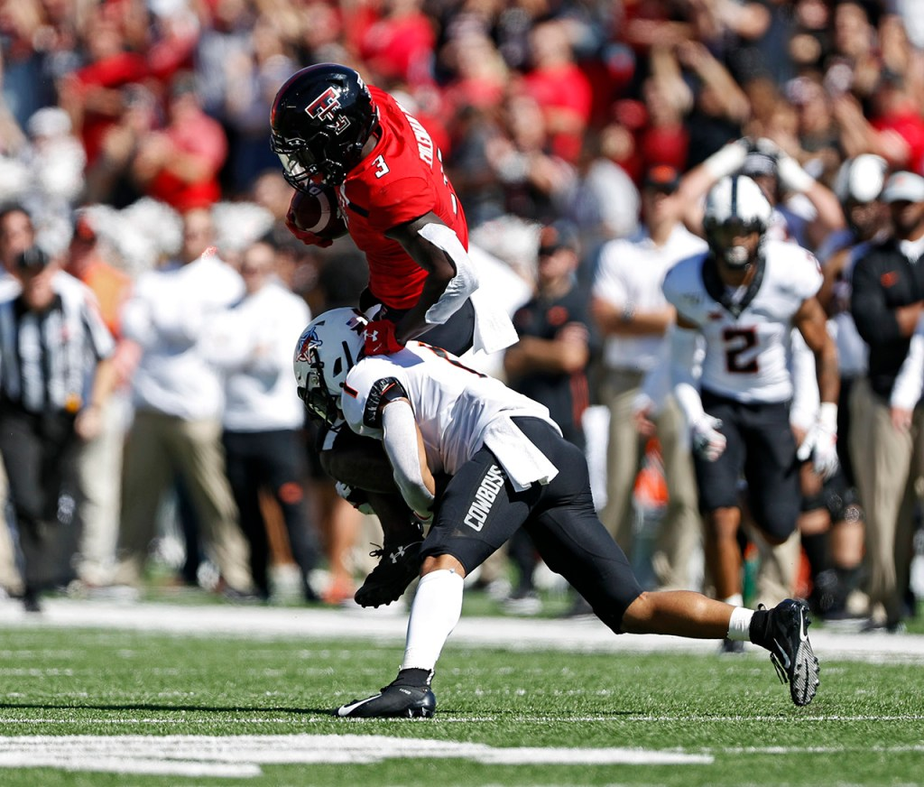 Oklahoma State's Landon Wolf (1) tackles Texas Tech's Douglas Coleman III (3) after he intercepted the pass during the game Saturday, Oct. 5, 2019, in Lubbock, Texas. (AP Photo/Brad Tollefson)