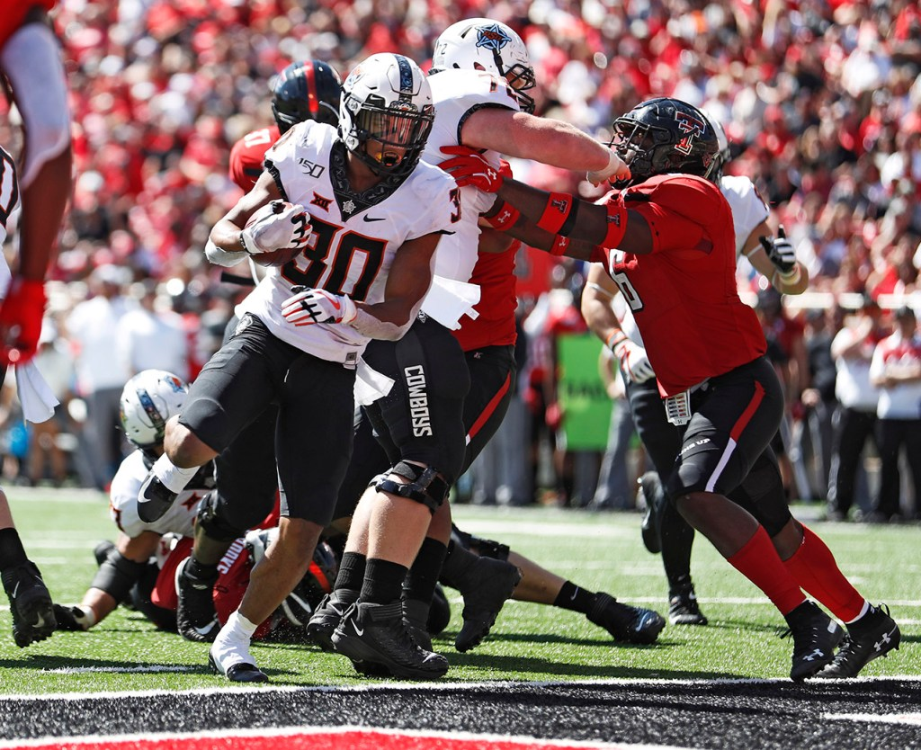 Oklahoma State's Chuba Hubbard (30) scores a touchdown during the game against Texas Tech, Saturday, Oct. 5, 2019, in Lubbock, Texas. (AP Photo/Brad Tollefson)