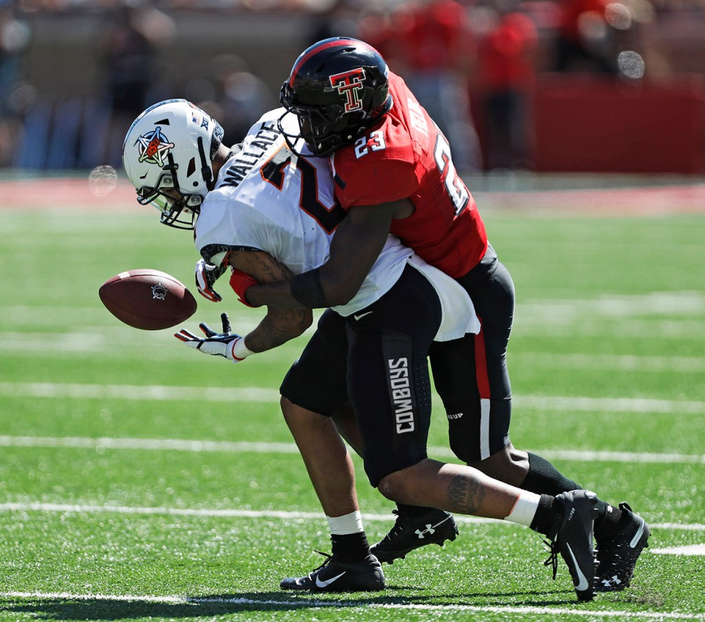 Texas Tech's Damarcus Fields (23) tackles Oklahoma State's Tylan Wallace (2) to break up a pass during the game Saturday, Oct. 5, 2019, in Lubbock, Texas. (AP Photo/Brad Tollefson)