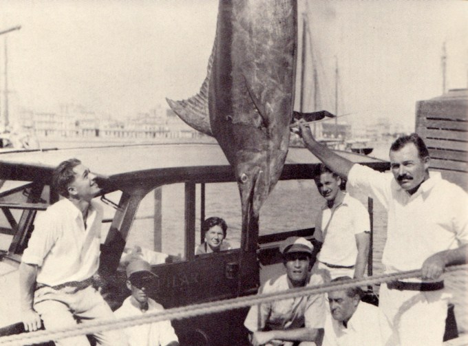 Hemingway shows off a 324-pound blue marlin as Samuelson (far left) admires it.