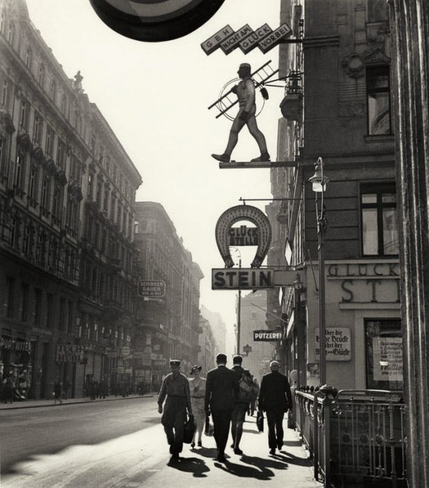 "Vienna in the 1930s. The sign, belonging to a gambling parlor, reads: ""Don't let luck pass you by."" A horseshoe and chimney sweep, superstitious symbols of good fortune, appear above. (Photograph:  Roman Vishniac)"