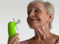 Photo: Older woman using hand-held fan