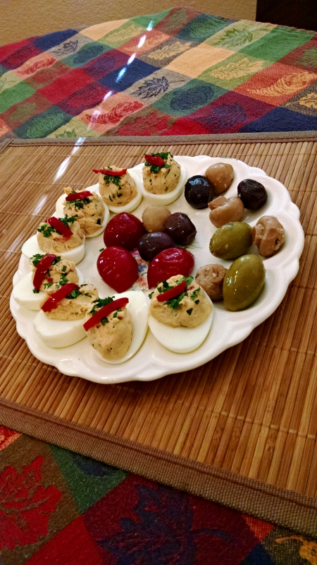 [image: deviled eggs with tuna alongside olives and marinated peppers/mushrooms]