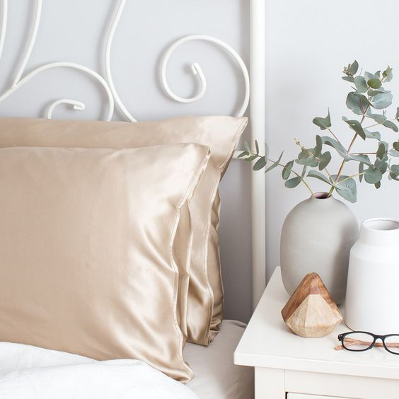 two slip silk pillowcases by bedside table