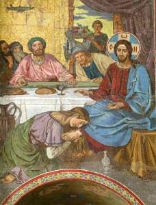 Syntinen nainen voitelee Jeesuksen jalat.