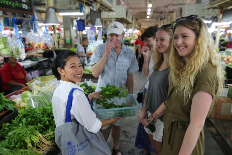 Shopping for ingredients and sniffing basil leaves in a market tour.