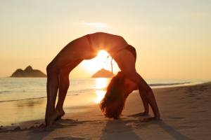 a confident girl doing yoga on the beach after full bikini waxing in Gainesville
